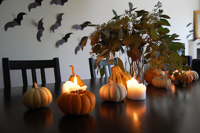 minimalist halloween decor and halloween tablescape using pumpkins, candles, and construction paper bats
